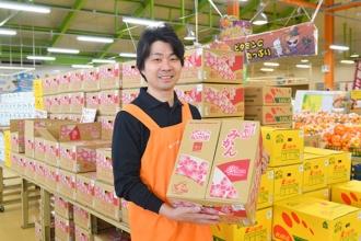 冬の果物の主役、みかんの箱を手にする岡田芳和店長(写真=水野浩志)