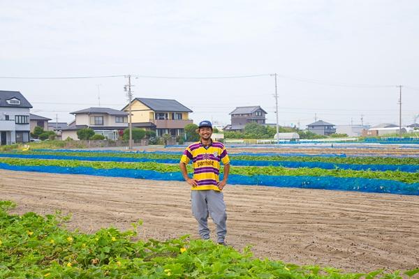 営農する畑で笑顔を見せる鈴木淳基さん。8月から3月までは玉ねぎづくりに全力を傾ける。その裏作として現在は冬瓜とさつまいもの生産をしている(写真:佐藤久)