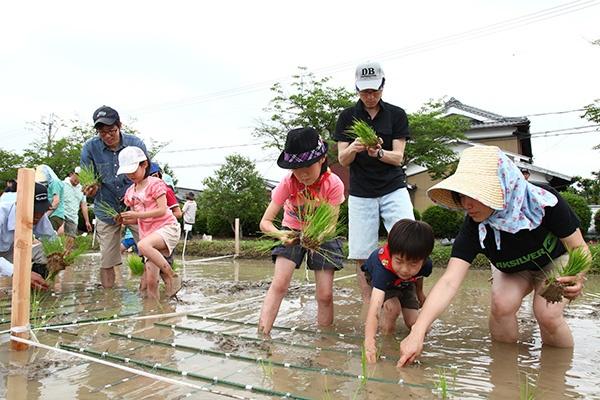 泥だらけになりながらの田植え。初めての体験に子どもたちは大騒ぎ<br>(写真:あきんどスシロー)